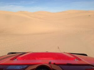 red off road vehicle pov in sand dunes